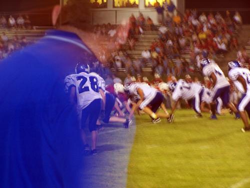 The Tigers line up on defense as Coach Norval watches from the sidelines.